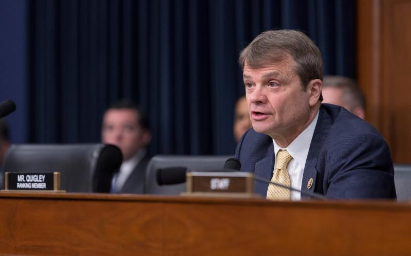 Quigley sits at a dias in a Congressional room behind a nameplate that says Mike Quigley Ranking Member