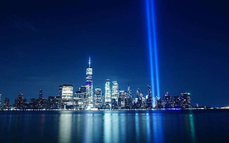 the new york city skyline at night with two light beams pointed toward the sky