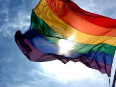 LGBTQ pride flag waves across sky with sun shining through the material