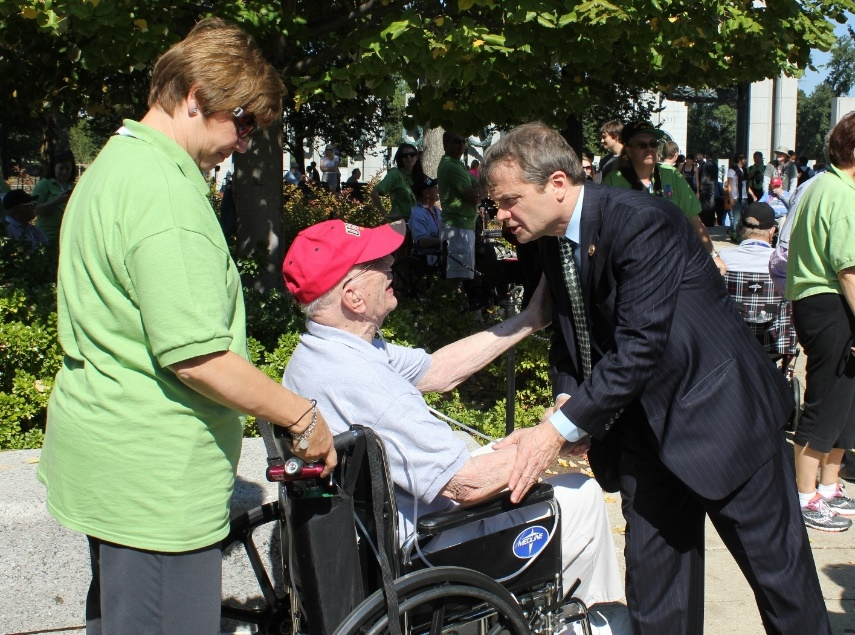 Rep. Quigley greets a veteran in a wheelchair during an honor flight visit.