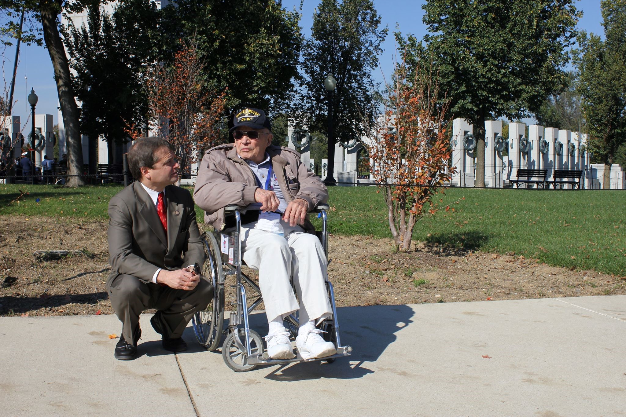 Rep. Quigley kneels on the ground to speak with a veteran in a wheelchair near the World War II Memorial in Washington, DC during an Honor Flight visit